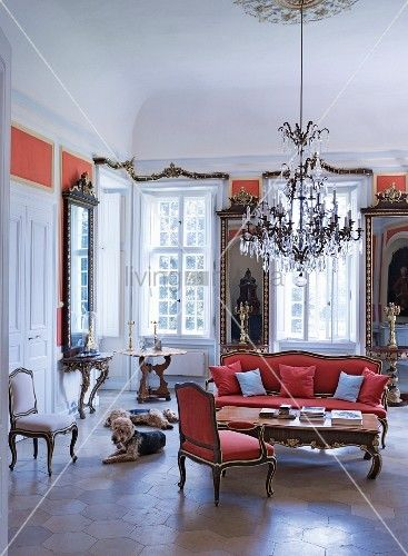A grand living room Castle Dennenlohe with a Rococo armchair and matching sofa with a chandelier above it and dogs sitting on the honeycomb-tiled floor