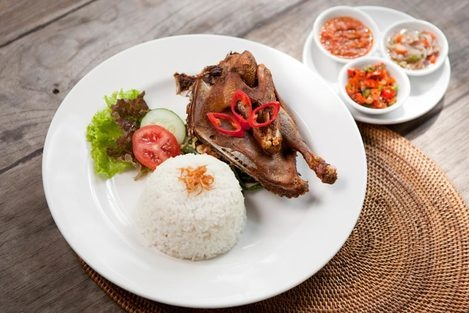 Bebek Semar  Crispy duck of semar warung on sauteed vegetables with steam rice and sambal.