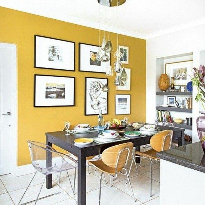 salon moderne avec une grande tables et des chaises transparentes ou en bois, mur jaune moutarde
