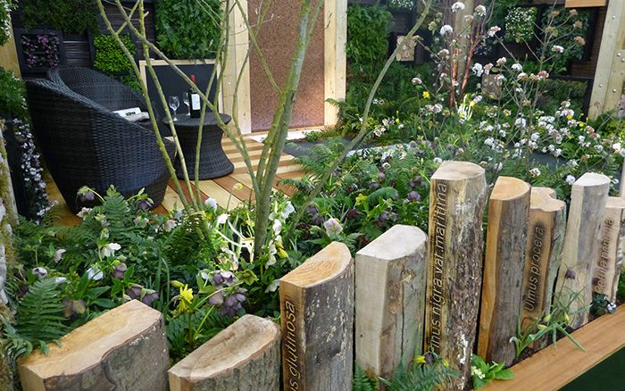 Clever timber fencing made by carving the tree species name into the side of logs with bark intact - design ideas from Askham Bryan College's show garden
