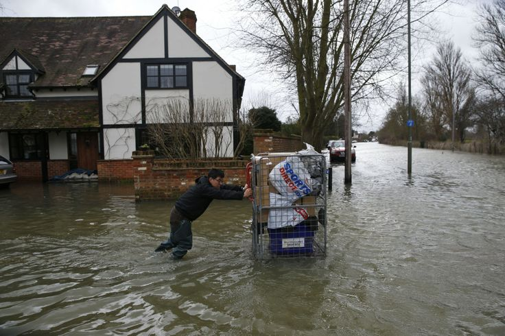 A resident pushes his belongings in a cart in the flooded town of Staines-upon-Thames