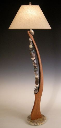 Stone Harp by Jan Jacque. Jacque continues her inspiration & fascination with stacked stones in this sculptural floor lamp. Graceful sculpted cherry provides the harp arch. Pit fired clay