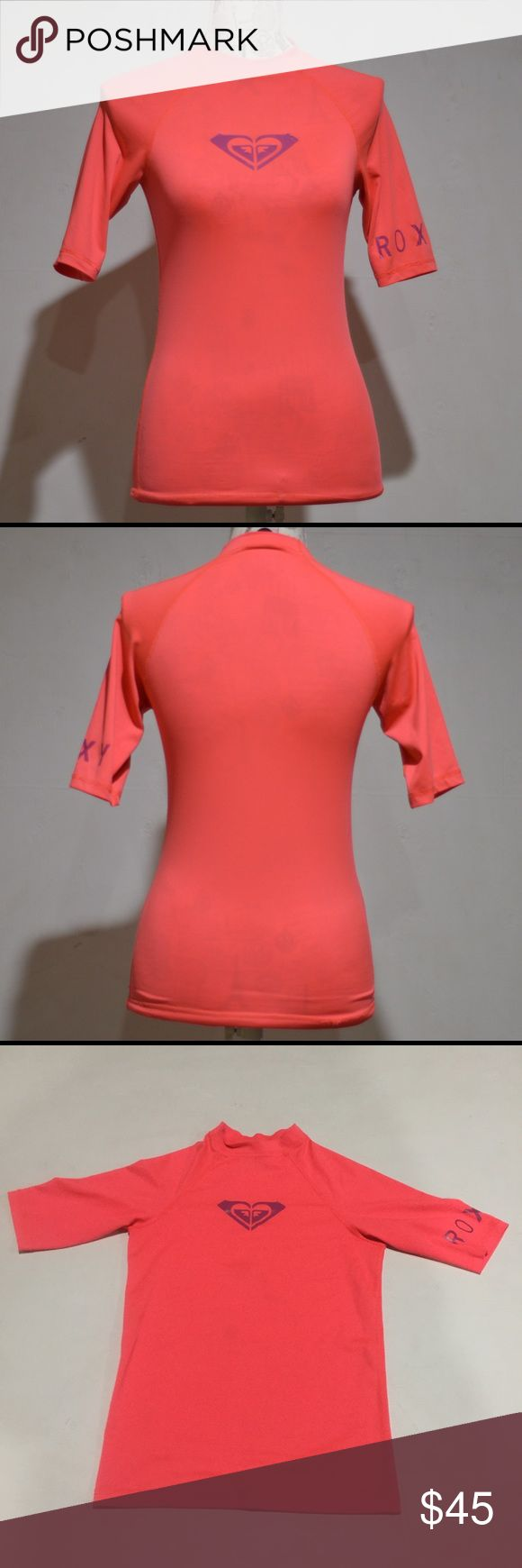 "💙Girls Roxy Rash-Guard Coral Pink Coral Roxy rash-guard Short sleeve. Fits adult small. Lots of stretch.  Defects: Faint discoloration on front, back hip seam popped. See pics. Condition:  Great  Length: 22"" shoulder to hem Bust: 15"" flat across Neck Opening:  7"" flat across  Model Lucy Shoulders 30"" Bust 35"" Waist 28"" Hips 35.5""  Smoke free home with cats and dogs. Washed in All Free & Clear. No Dry clean or stain treatments due to skin allergy. Roxy Swim Rashguards"