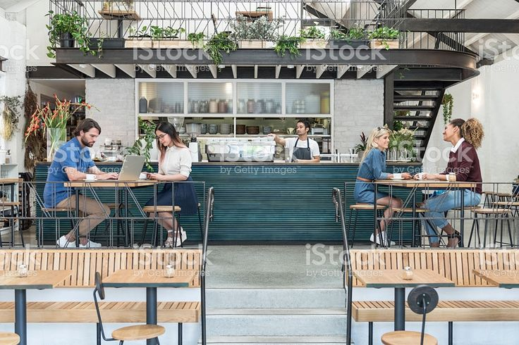 Customers in modern cafe with drinks and laptop royalty-free stock photo