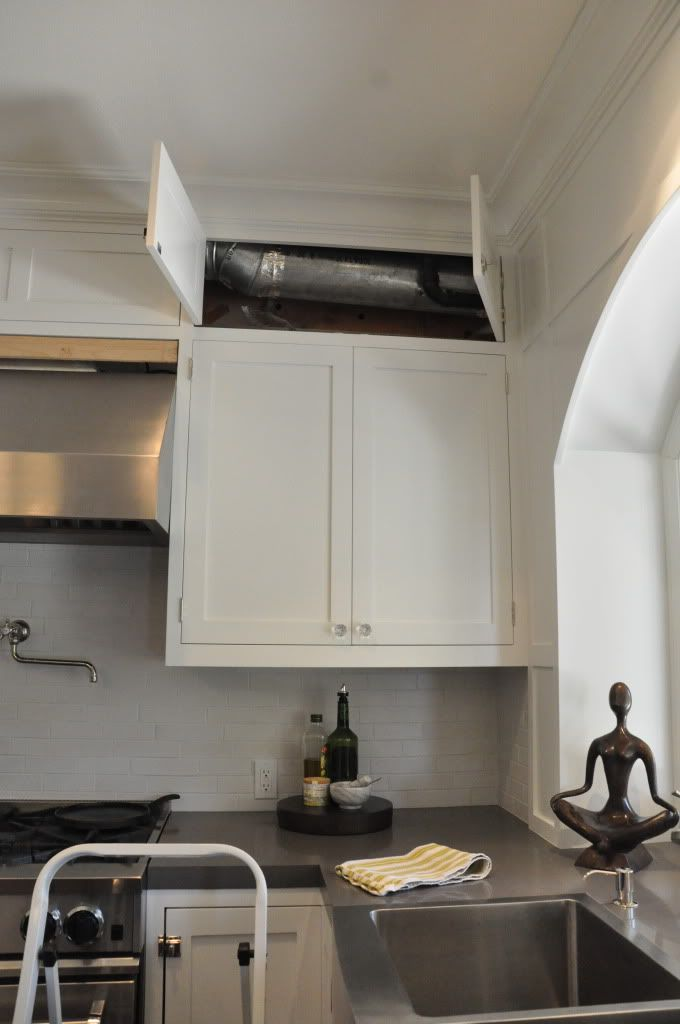 Couldn't get rid of soffit so they made doors so it looks like faux double cabinets! Brilliant!