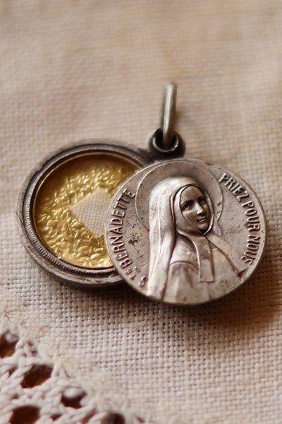 ルルドの泉で聖母の出現の奇跡を体験したベルナデッタの姿を描いたメダイ。後に修道女となり、1925年に列福、1933年に列聖。こちらは列聖記念に作られた、1933年ごろの製造のものだと推測されます。スラ…