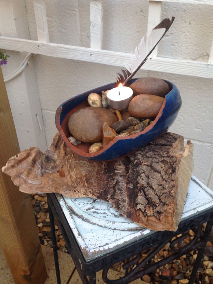 It amazing what one can do with, a broken pot, a few stones, a crow feather and a tea light candle
