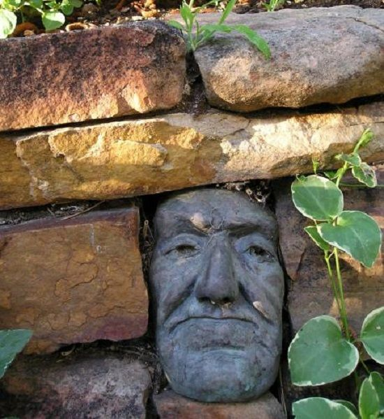 stacked stone wall - Incorporate a face, by Jerry Boyle. www.boylesculptures.com