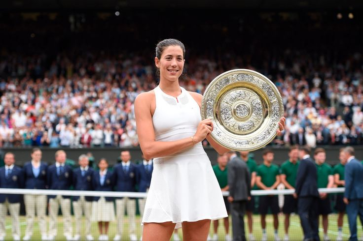 Garbiñe Muguruza poses with the Ladies' Singles Trophy on Centre Court following her victory over Venus Williams in straight sets