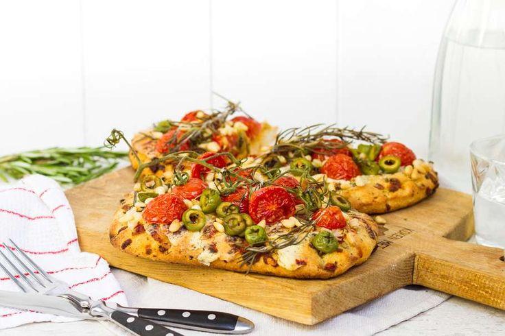 Tomatenfocaccia belegd met olijven, pijnboompitten en rozemarijn