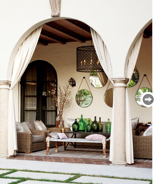 A grouping of round hanging mirrors looks casually chic on this covered terrace. {PHOTO: Donna Griffith}: