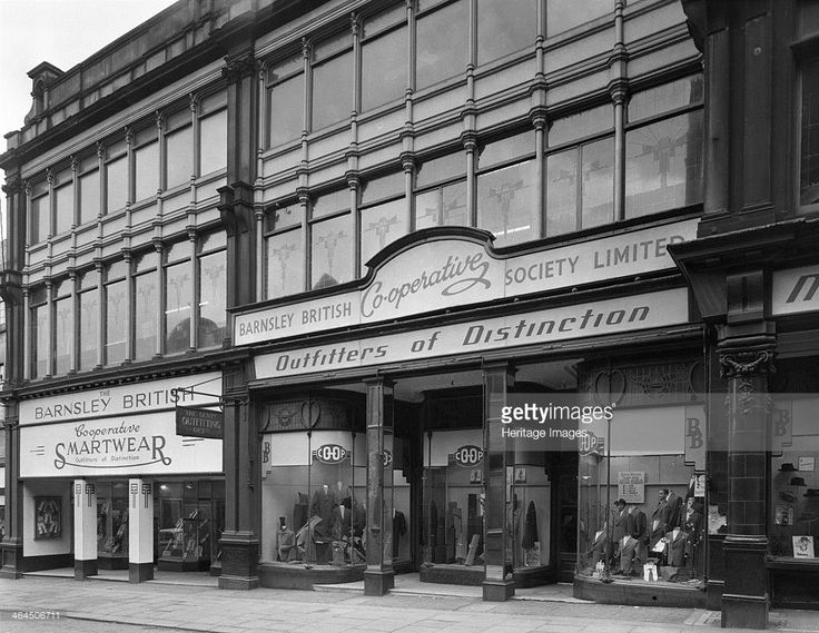 Exterior of the Barnsley Co-op central men's tailoring department, South Yorkshire, 1959. The shop windows show displays of schoolwear for…