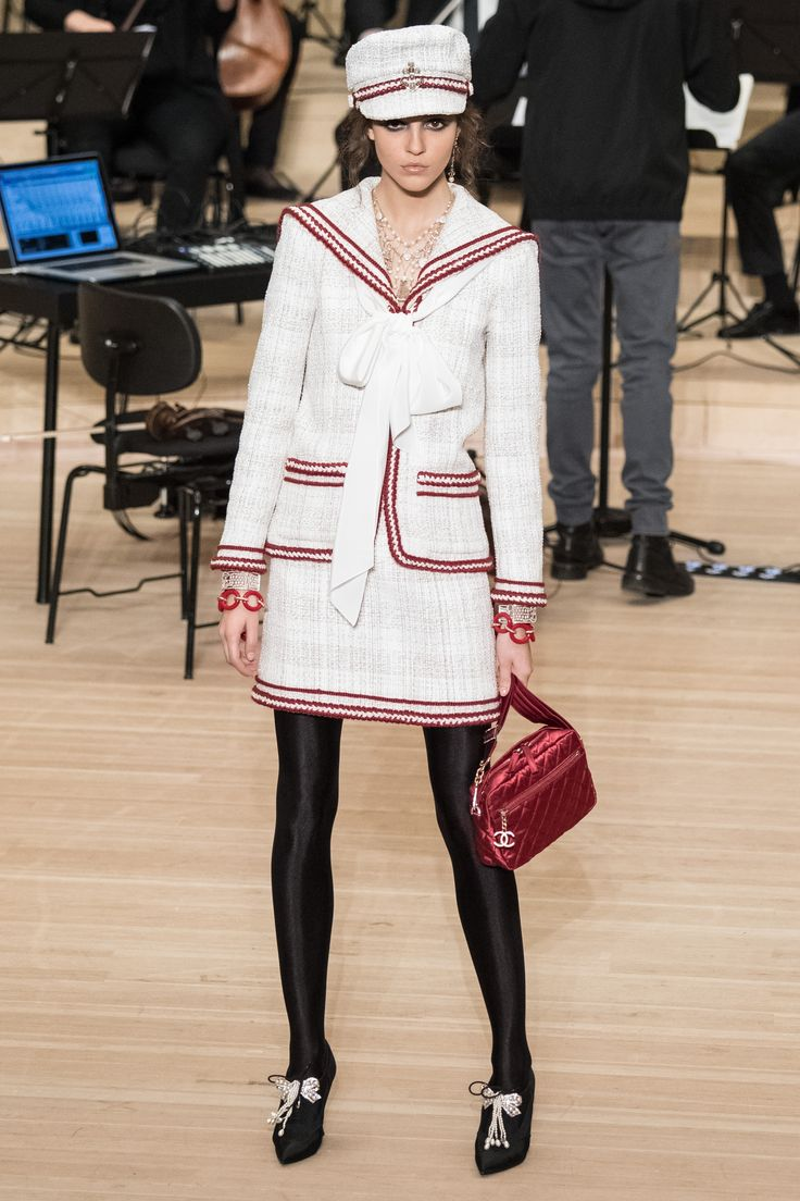 A model wears a white Chanel suit complete with bow detail and red quilted bag at the Chanel pre-fall 2018 show.