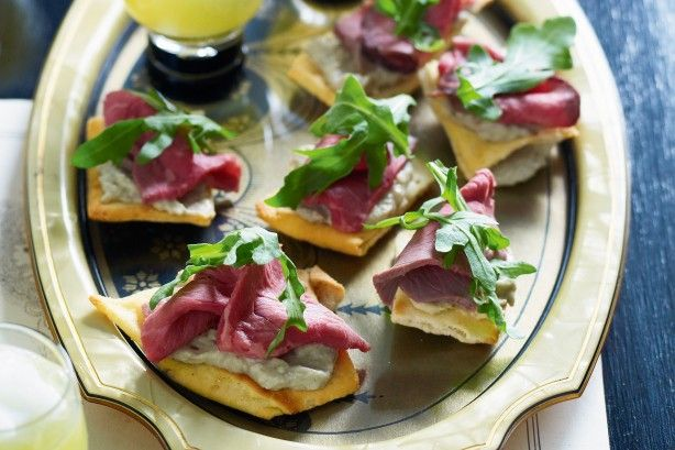 Sesame garlic pita crisps are a tasty base for these crunchy canapes topped with smooth babaganoush, roast beef and peppery rocket.