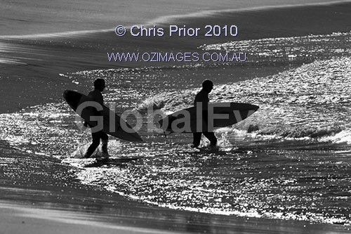 silhouetted surfers. two mature aged surfers enter the water at the start of an over forty  years division heat. Stock Photo By Chris Prior