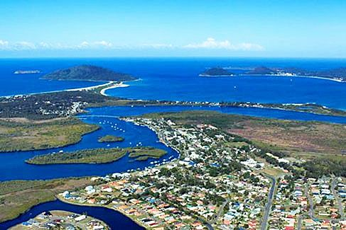 Tea Gardens, NSW, Australia - 220km north of Sydney / Tea Gardens in the foreground and Hawks Nest across the Singing Bridge on the opposite side of the Myall River. Yacaaba Headland extends out on the left and Tomaree on the right at the entrance to Port Stephens Photo / https://www.facebook.com/teagardens.hawksnest