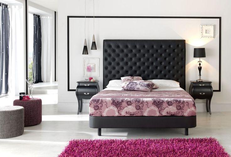 schwarz gestrichene Zierprofile bilden einen Rahmen hinter Bett