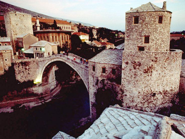 L'arcuato ponte di pietra di Mostar attraversa il fiume Neretva nella Bosnia Herzegovina. Il ponte fu costruito nel 1566 su ordine di Solimano il Magnifico, per rimpiazzare un vicino ponte di corda considerato insicuro dai suoi sudditi. Essere parte dell'Impero ottomano aveva dei vantagg