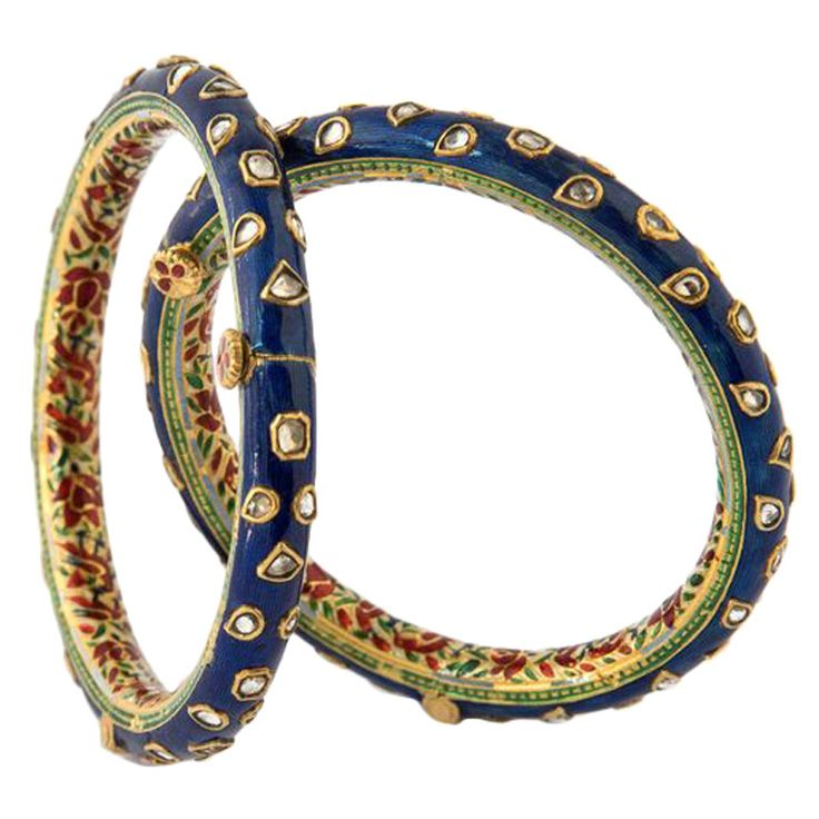 Indian Churin Enamel Sapphire Gold Bangle Bracelets Early 20th Century. A pair of gold bangles, CHURIN, of which the outer side is decorated with dark blue, Nil Zamin enamel, kundan set with white sapphire in gold collets, shaped like leaf and flower buds. The inside is decorated in a floral pattern with Safed Chalwan enamel, red and green enamel on a white ground, North India, Rajasthan, Jaipur, early 20th Century