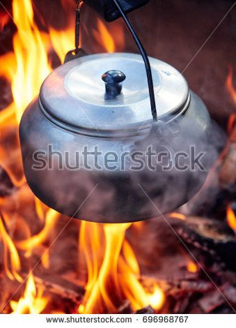 Stock Photo: Metallic coffee pot in campfire heat while hiking. Wood burning with flames beneath the pot. -