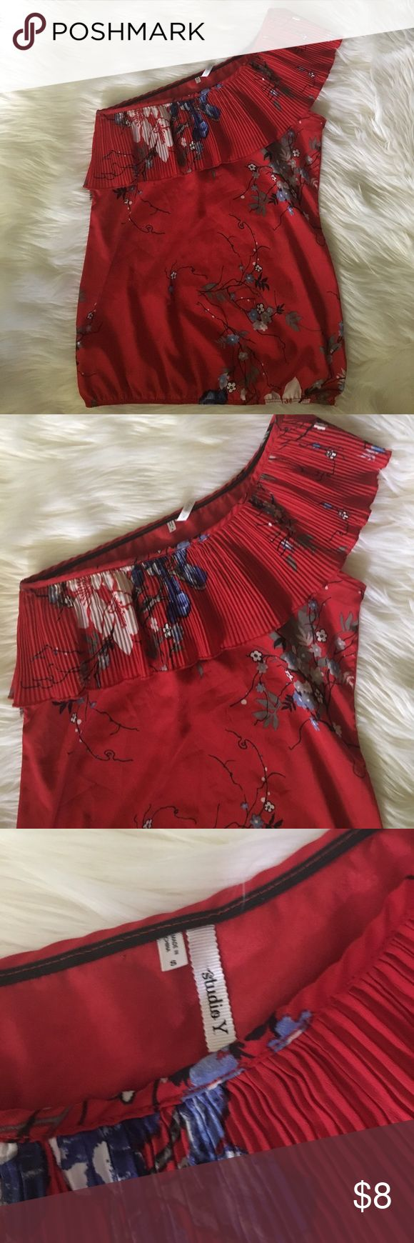 Studio Y one shoulder top Red floral print one shoulder top. Good used condition. Studio Y. I believe this brand is sold at Maurice's? There is a tear on the side with no sleeve, underneath the ruffle. The ruffle covers it, but I will repair it and update the listing when I do. Studio Y Tops
