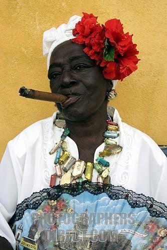 Otra mujer cubana en el vestido tradicional, fumando un gran cigarro. Me encanta el collar que está llevando, muy colorido y elegante. Creo que ella está agarrando un abanico.