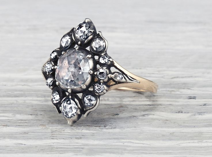 Rare Antique Georgian engagement ring made in yellow gold and silver and centered with an approximate 1 carat Dutch rose cut diamond. Circa 1860. Beautiful Georgian cluster with just the right amount