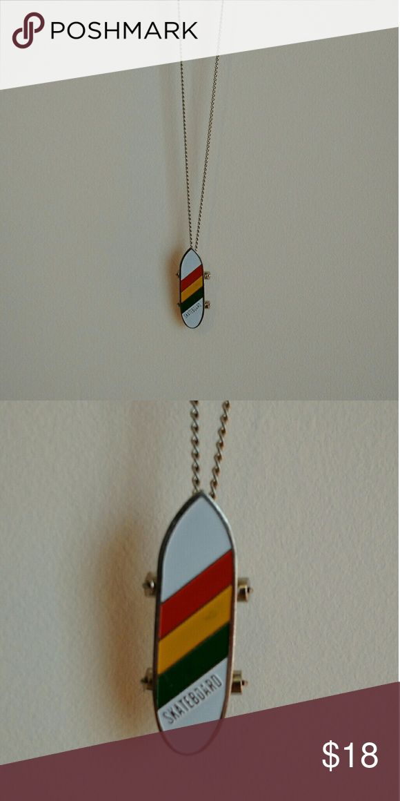 "Vintage Skateboard Necklace 8"" length 2"" pendant White skateboard with orange, yellow, and green stripes. Little wheels move.  🌸If you need anymore information please feel free to ask! Jewelry Necklaces"