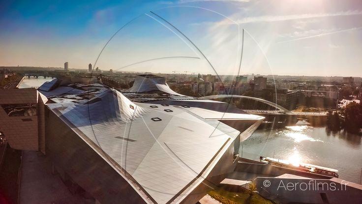 https://flic.kr/p/wQRXyZ | Musée de la Confluence au levé du jour | Photographie par drone de la pointe sud du Musée de la Confluence au levé du jour, avec en arrière plan la ville de Lyon et le flare du soeil levant dans l'objectif. On distingue au loin les 3 tours du quartier des affaires de la Part Dieu (le crayon, la tour Incity et la tour Oxygène).