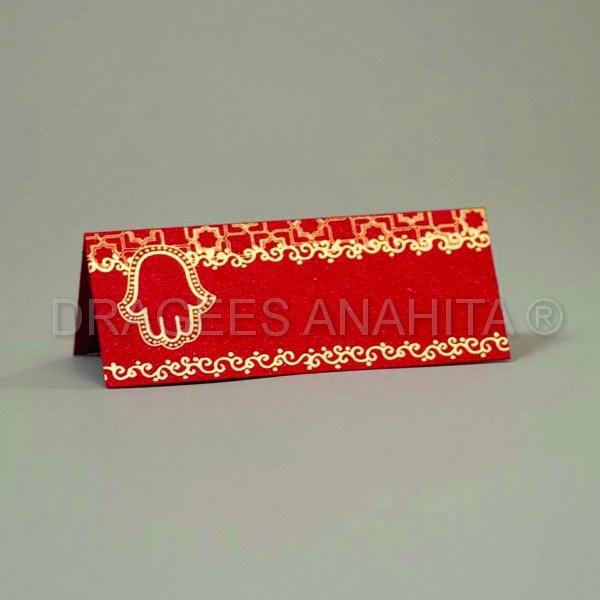 Un marque place rouge avec une main de fatma en or et un motif moucharabieh, une touche d'orient dans votre cérémonie.