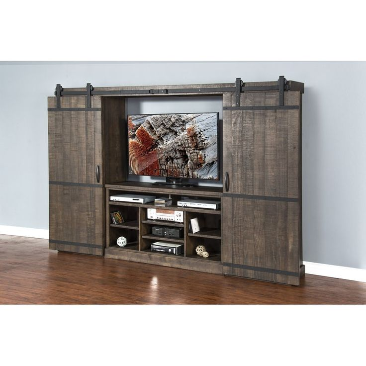 Brimming with farmhouse flair, this rustic entertainment center is the perfect anchor for a rustic family room ensemble. Made from natural barn wood, this weathered design is defined by two sliding barn doors that open to expose a television stand that includes cable management grommets and nine adjustable shelves—perfect for the cable box, DVD player, and all your favorite gaming consoles. When the doors are closed, you have access to six display shelves for books, movies, records,...