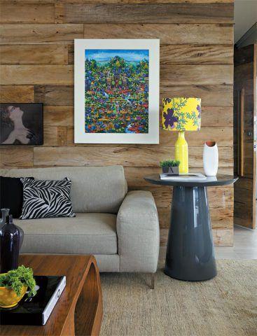 """Licença para ousar. É o brilho da laca que faz a graça da mesa lateral cinza-chumbo Jone (Dpot), escolhida para compor a sala do apartamento de um jovem casal. """"Embora de tom discreto, a peça tem glamour e confere sofisticação à madeira de demolição, que reveste a parede"""", explica a designer de interiores Karina Salgado, sócia da In House Design. O móvel também aceita a companhia de matizes mais luminosos, caso do amarelo do abajur (Sandra Romanoff para Studio In House)."""