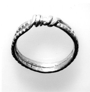 10-11th C. Greater Manchester, England. Gold finger-ring with double spiral hoop and ends coiled round the back; raised lozenges and pitted decoration.