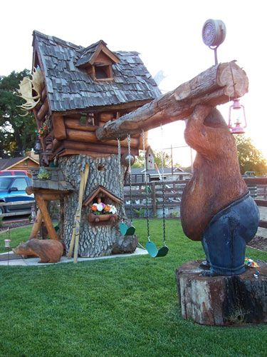 A burly bear wood carving holds up a custom swing set for this amazing rustic playhouse