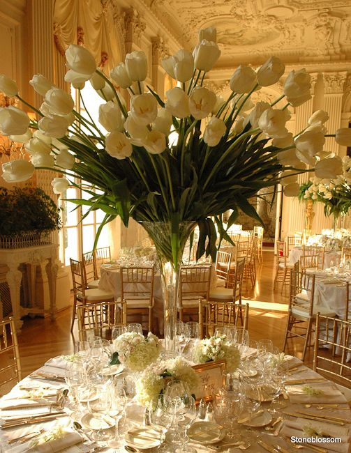 "Nothing more beautiful than the French Tulip! For the tall centerpieces is a lovely idea to tuck little floral touches at the base. Perhaps the floral on the napkin is a touch I would eliminate...even though I always feel there is no such thing as ""too much""...this might be the exception to a very full table!"
