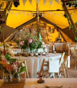 Bunting, ivy garlands and gorgeous florals in recycled jam jars for a tipi wedding.