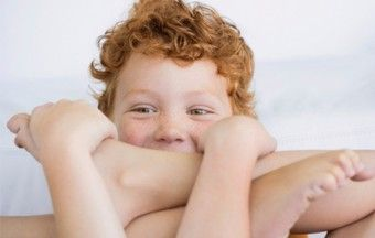 Image of boy holding his feet. Can you catch Hand-Foot-and-Mouth Syndrome twice?