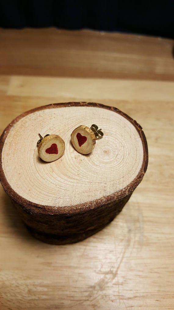 Orecchini in legno di arbusto selvatico in tre versioni di cui uno senza disegno a 7 euro, una con cuore rosso e una con stella arancione a 10 euro.  DISPONIBILI A MONACHELLA SU RICHIESTA (prezzo invariato).  Su richiesta posso effettuare varianti sui colori.  La dimensione è una circonferenza di 1 cm di diametro circa, la dimensione può variare di qualche mm in più o in meno. Il contorno è irregolare come il ramo da cui è tagliato lorecchino.