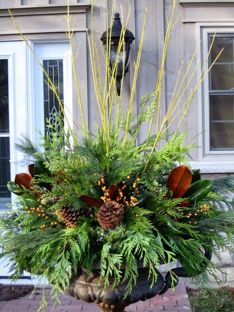 Urn decor - mixed greens, pine cones, berries, magnolia leaves, sticks