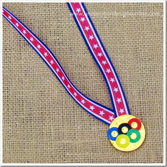 olympic gold medal treats from chocolate coins, ribbon, and paper reinforcements colored in olympic colors.