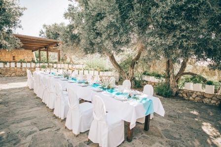 Wedding reception dinner set up under the ancient olive trees at traditional private estate in Crete. MOMENTS www.weddingincrete.com