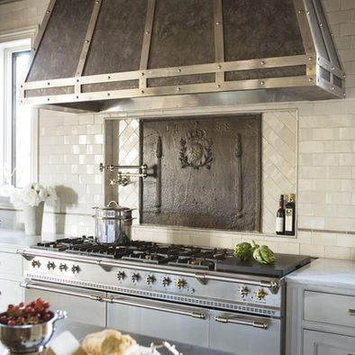 """Carrara marble countertops, stainless steel French Lacanche range, custom designed zinc and steel range hood, Waterworks and Sonoma Tilemakers backsplash tiles, custom designed cabinetry crafted by Jose' Florez, two Sub-Zero refrigerators, Miele' dishwasher, speed oven, and integrated coffee system Shaw"""" bad ass Hood"""