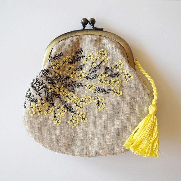 ミモザ柄のがまぐちです。ミモザの柄をガリ版で手刷りし、花の部分をを手刺繍しました。内側は空のような青いリネンに、黄色い水玉柄のチュールを重ねています。ポーチとして使える大きさのがまぐちです。化粧品を入れても良いですし、お財布としても。素材:リネン(外布、内布)、コットン(タッセル)、チュール、口金大きさ:約14cm×15cm(タッセルはのぞく)