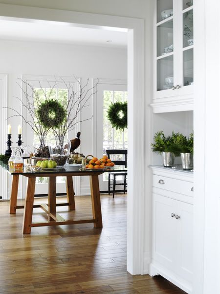 Add festive greenery to areas set up for entertaining. The farmhouse-style glass-topped trestle table adds counter space and keeps the kitchen casual. The versatile design means the homeowners can pull up chairs for an informal dinner, arrange a breakfast buffet for guests, or display appetizers at a bustling cocktail party.