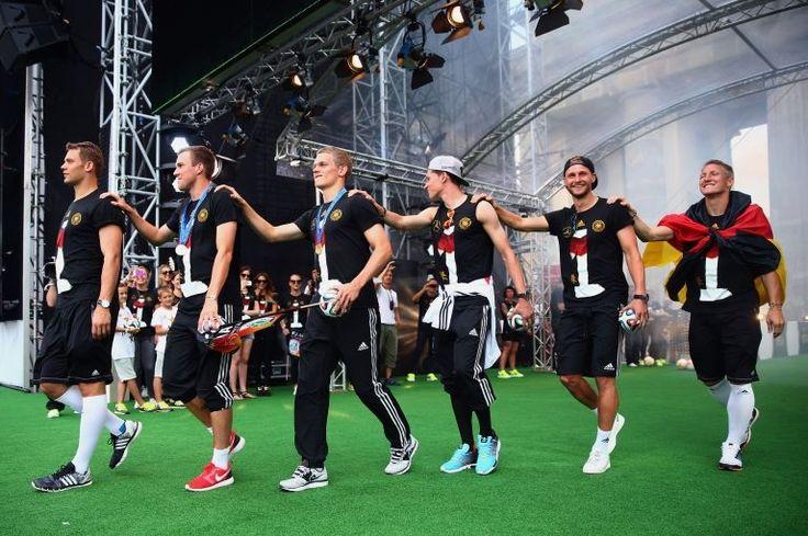 Manuel Neuer, Kevin Grosskreutz, Matthias Ginter, Julian Draxler, Benedikt Hoewedes and Bastian Schweinsteiger (L-R) celebrate on stage at the German team victory ceremony