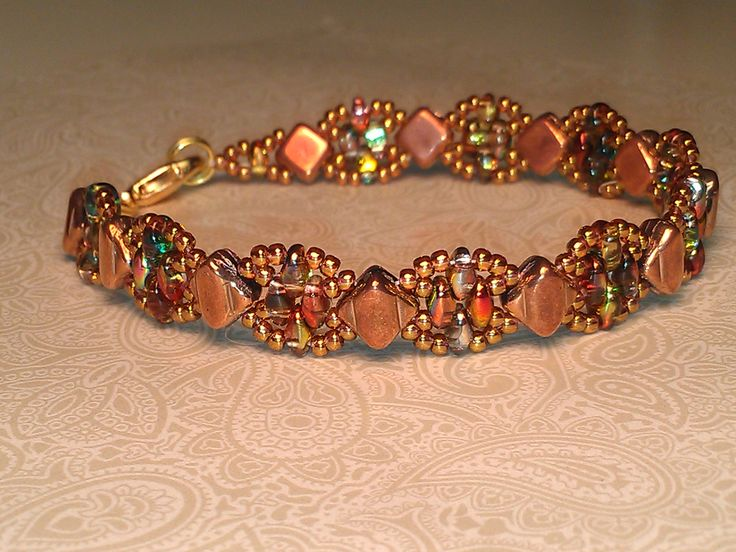 """""""Silky Stacker"""" from Deborah Roberti """"around the beading table) Silky beads in jet capri gold, superduos in crystal red yellow and 11/0's in toho gold pink lustered transparent. Another great pattern from Deborah!"""