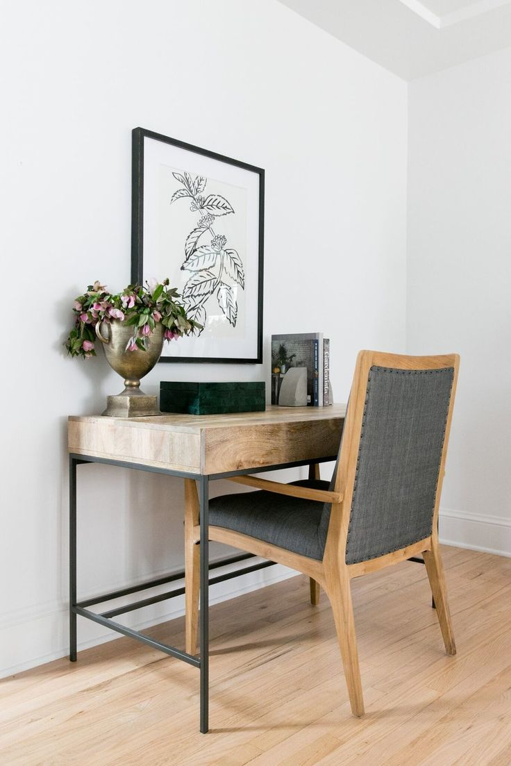 Metal and wood desk with beautiful wall artwork. brass urn modern chair w/gray flannel
