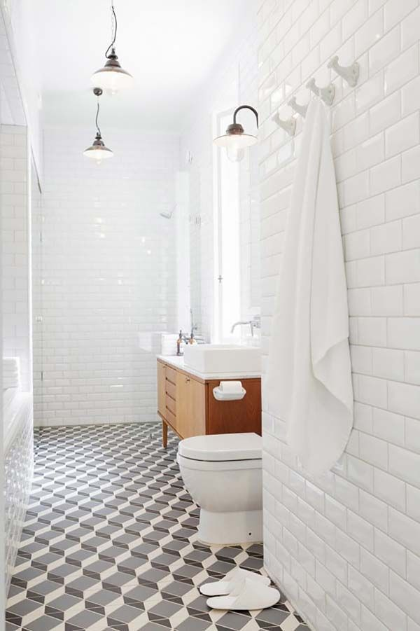 Midcentury walnut vanity, white subway tile, and geometric black and white floor.
