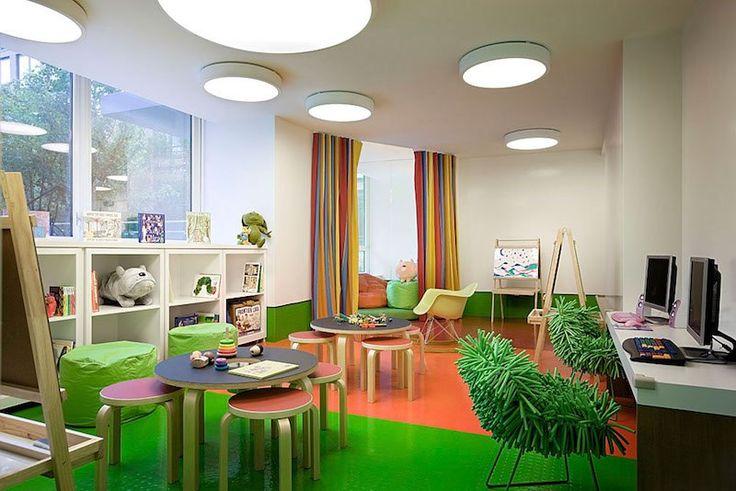 salle de jeu en blanc et vert gazon avec tables de jeux, rideaux rayés et plafoniers