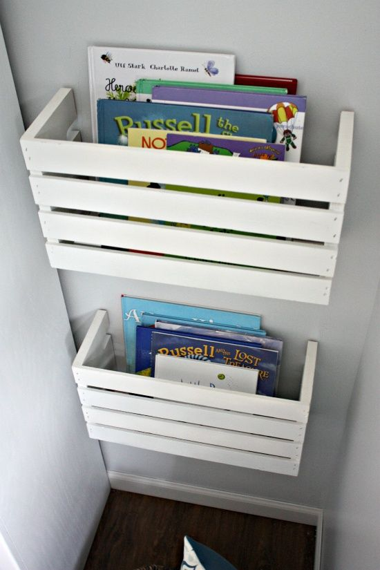 Find a wooden crate at craft store, paint any color you want, cut in half with table saw, attach hanging brackets with screws and attach to wall. Immediate eye catching book storage for little ones - priceless!.